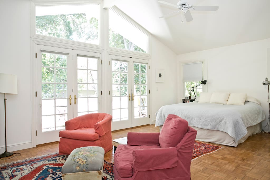 Light-filled master bedroom with sitting area and TV, opens onto deck over shady, quiet backyard.