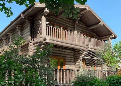 Дом-шале из северной сосны среди лесов и полей