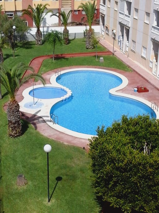 grande piscine avec ses abords en pelouse et une petite pataugeoire pour les enfants