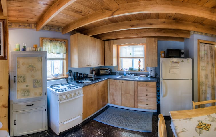 A full kitchen with microwave, and coffee maker.