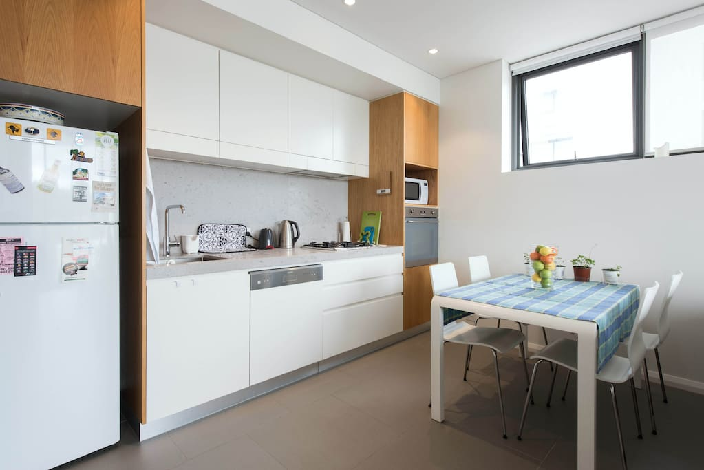 Kitchen with microwave, kettle and fridge and cutlery.