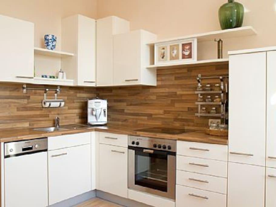 Vollausgestattete Wohnküche mit E-Herd, Geschirrspüler, Kühlschrank und Kaffeevollautomat