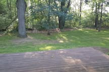 Back deck overlooking the woods. LOTS of wildlife (the good kind). Has a patio table and chairs.