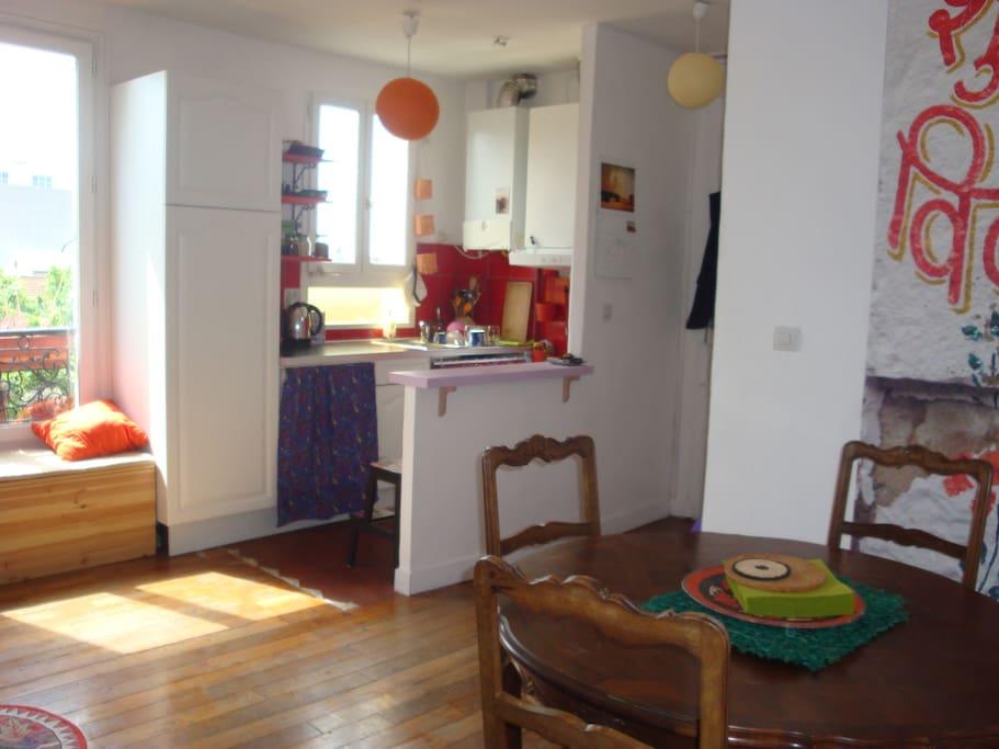 La table à manger, et la cuisine américaine équipée (frigo, gaziniére, lave vaisselle, etc.).