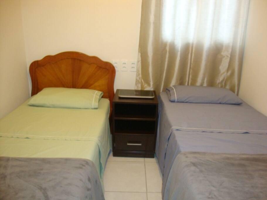 Quarto com duas camas de solteirão e aparelho de ar condicionado.