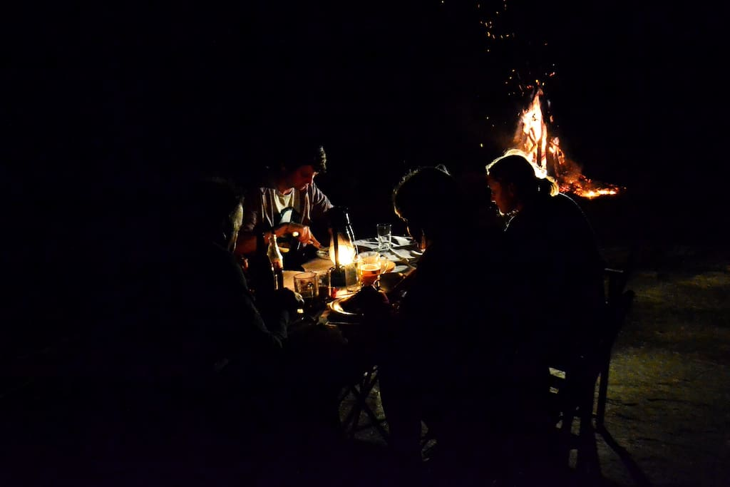 Guests enjoying dinner by the Camp fire