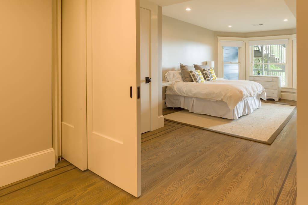 Large and restful bedroom has with new queen bed. Sliding pocket doors can be closed for privacy or left open to provide more space.