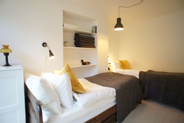 Twin bedroom with a door leading to the courtyard garden. Quality bed linen and towels provided