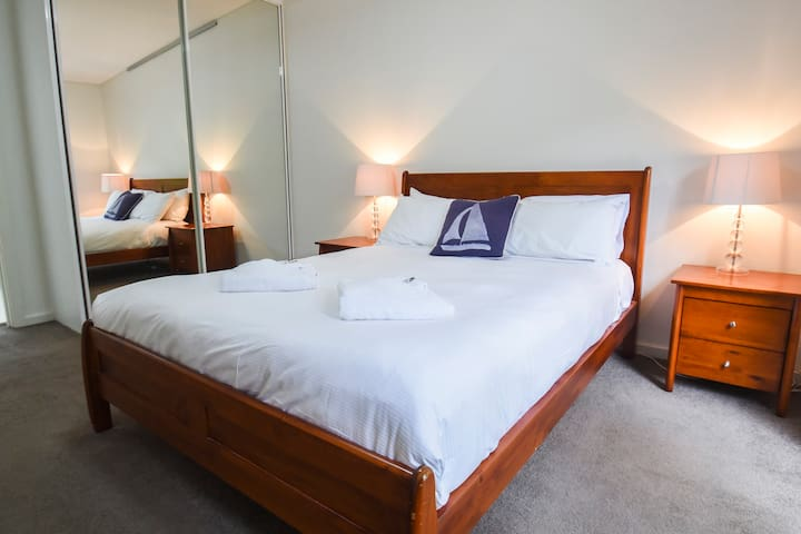 The master bedroom comes with a Queen size bed, a wardrobe with a full-mirror slide door, an ensuite, and a small balcony