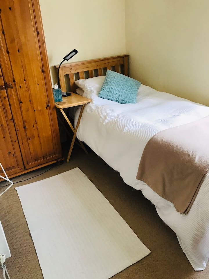 Single bed in very cosy bedroom.With single wardrobe and chest of drawers