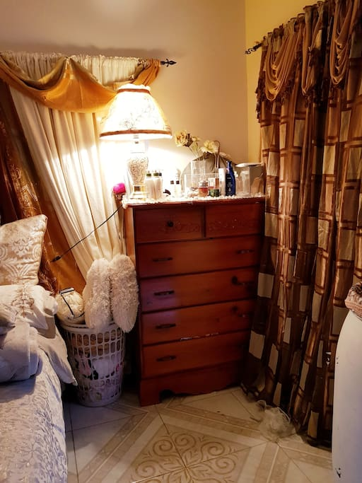 A Large Chest Of Drawers with a Lamp, near a Large window. Completed with a basket which contains extra beddings, and sleep masks.