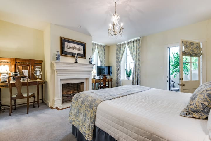 King bed in the bedroom with fireplace and private entrance to veranda
