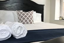 Queen-size bed with fresh linens and towels