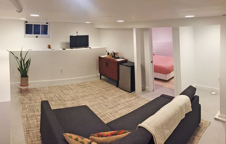 Bright, spacious den/living area with sleeper sofa, tv, mini fridge and coffee station.