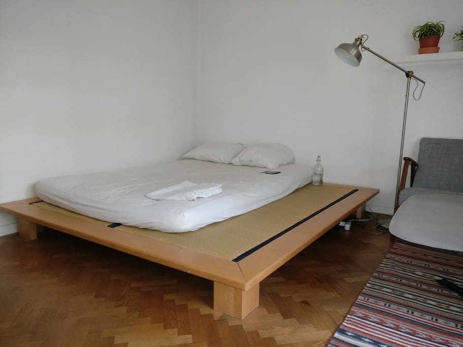It's a queen sized bed - the edge is used as a bench alongside the table