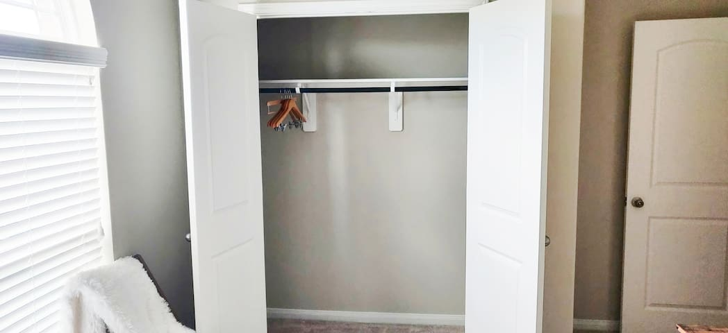 Full size closet with hangers provided for storage.