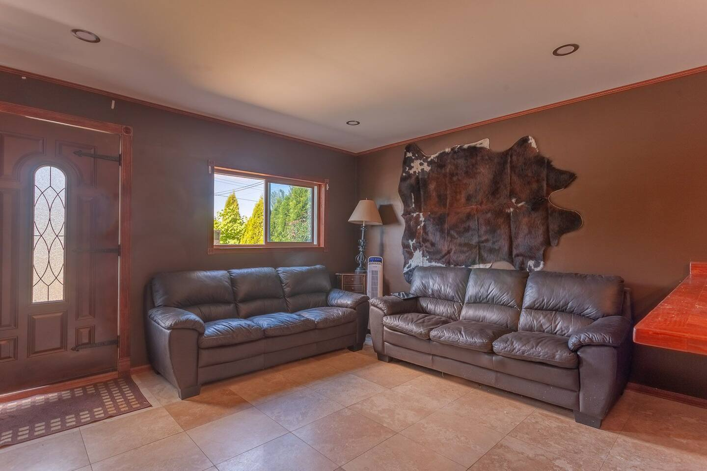 Living room with heated floors, leather couches, 80inch LCD flat screen TV, and bar fridge