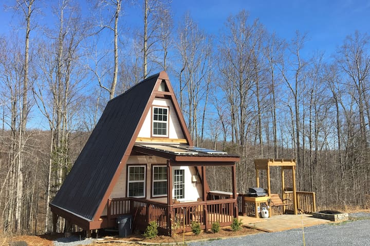 """Welcome to """"Off the Grid"""" and enjoy outdoor living at our Mountain Retreat.  Note the gas grill, fire pit, and beautiful patio and deck.  Sitting on the swing as you watch the stars is breathtaking! Views are beautiful!!"""