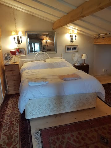 Bedroom 4 with king size bed. Side tables with fan and lamps. Smoke alarm. Ensuite bathroom, Air conditioned, rails for hanging clothes, chest of drawers ,persian rugs,