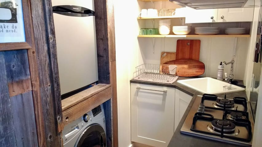 Kitchen has small (not mini) fridge with separate freezer and washer/dryer in-one laundry unit.