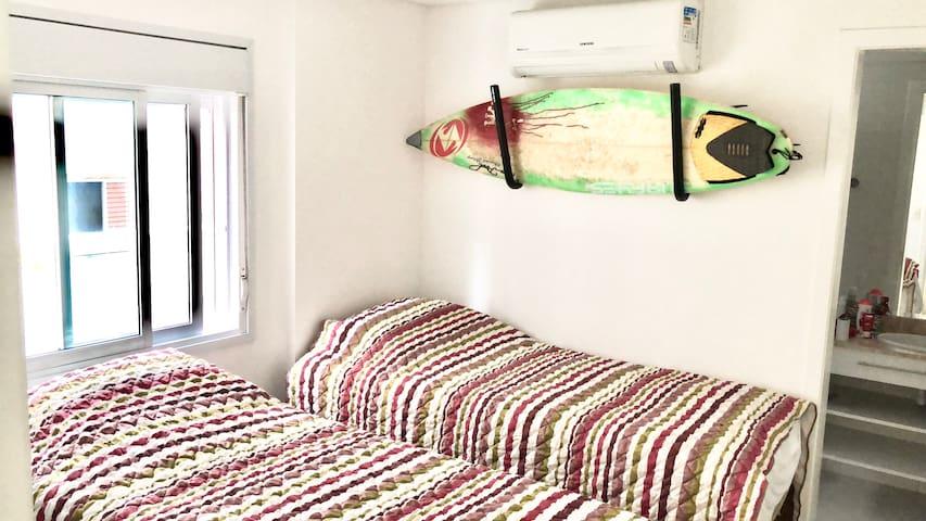 Suíte 3 com 2 camas de solteiro, colchões super confortáveis, travesseiros de pena de ganso e ar Condicionado com controle remoto.