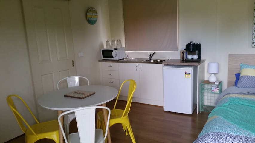 Kitchen with fridge, microwave, cooking hotplates & utensils