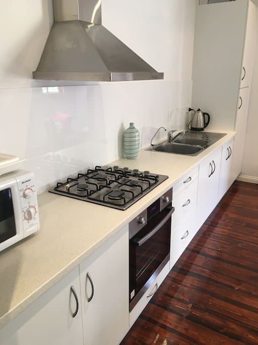 Kitchen with full amenities. Microwave, oven, gas stove, toaster, kettle and fridge.