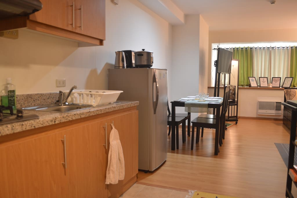 From this view, you can see our kitchen sink (cleaning supplies are under the sink), cupboards (cookware, cooking utensils and dinnerware are in the overhead cabinets), fridge and dining area.