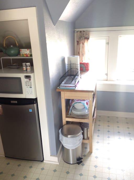 Mini-kitchen with fridge and microwave.