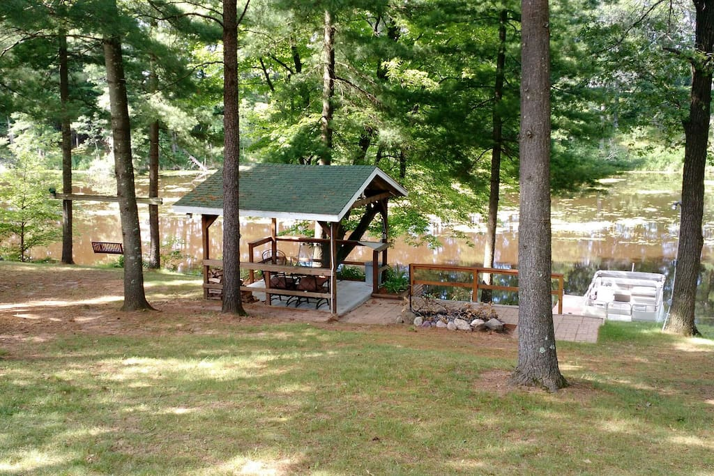 12'x12' pavilion and firepit near water's edge.