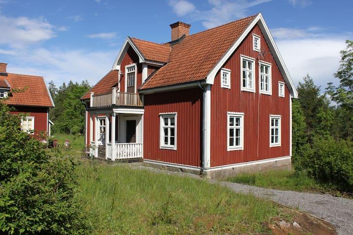 Högt belägen gård med sjö och skog inpå knutarna