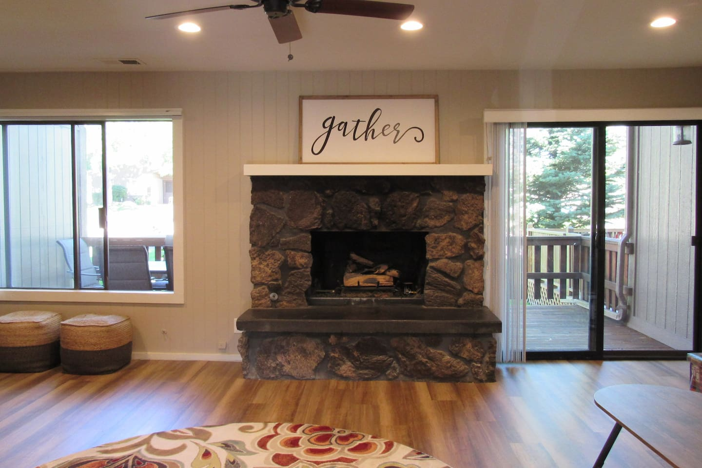 Open living room with fireplace and door to deck