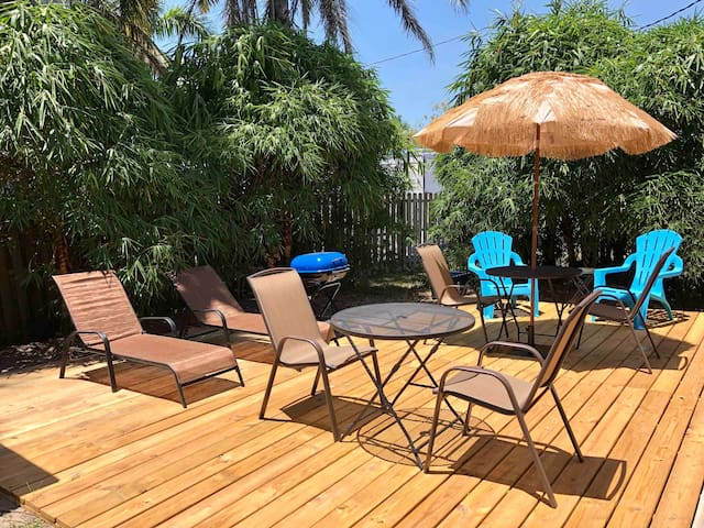 This sunny and relaxing deck with bbq grill in the backyard offers dining table, umbrella, and sun beds. It will be shared with the guests residing in the other side of the duplex.