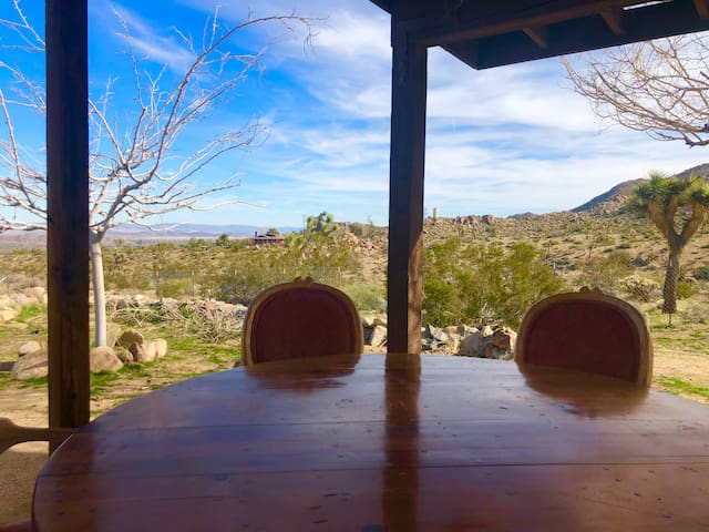 The back yard with a fire pit and lounge area looks into an unobstructed 360 views of Joshua Tree.