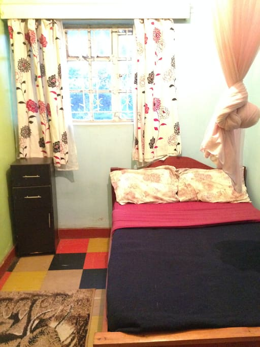 One of our single occupancy rooms, including double bed (with mosquito net), drawers and wardrobe.