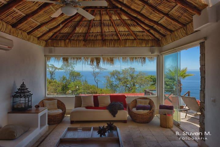 Sala de estar con la vista a la alberca y el Pacífico - techos altos de palma (palapa) encajan perfectamente al ambiente playero