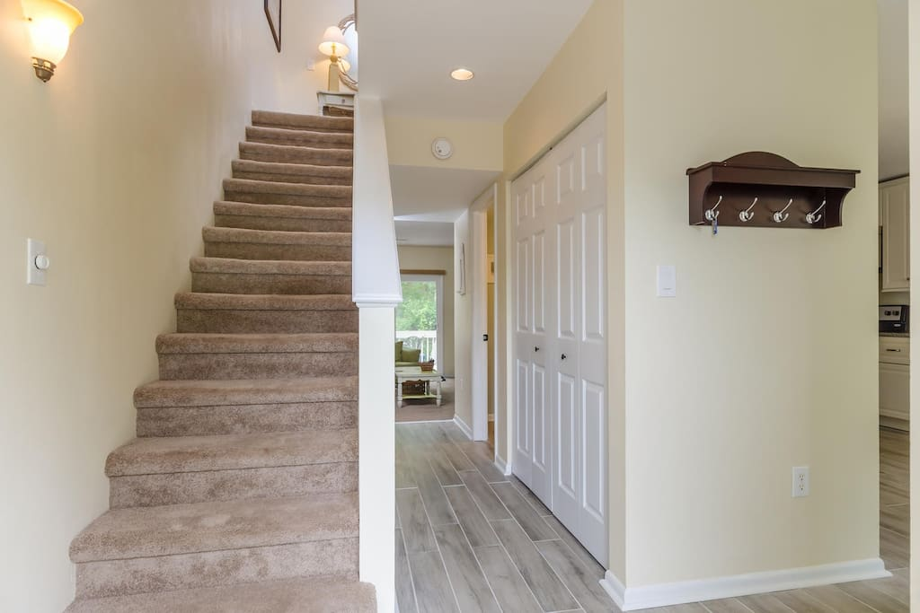 Spacious entryway leading to laundry closet and living room beyond