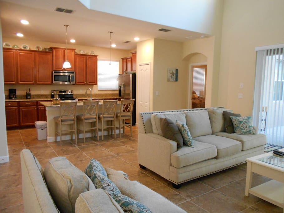 Large family room opens to gourmet kitchen with granite counters and stainless steel appliances.