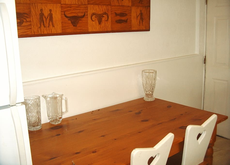 Pine  kitchen table and handmade pine chairs; hand carved zodiac tabletop, and entrance to the enclosed back yard with outdoor table, garden. You have access to everything but the stove and oven.