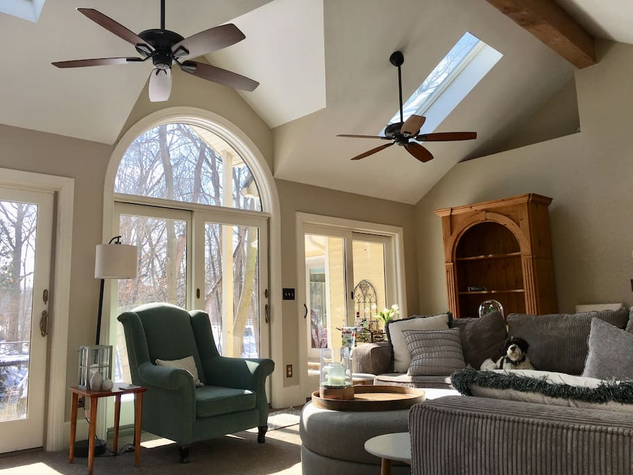 The great room with three sets of sliding doors. The center doors go out to a slate patio overlooking the creek. The armoire contains cards and board games for your family members to enjoy.