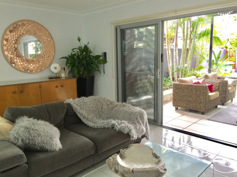Open plan living room flowing out onto lovely tropical outdoor living.