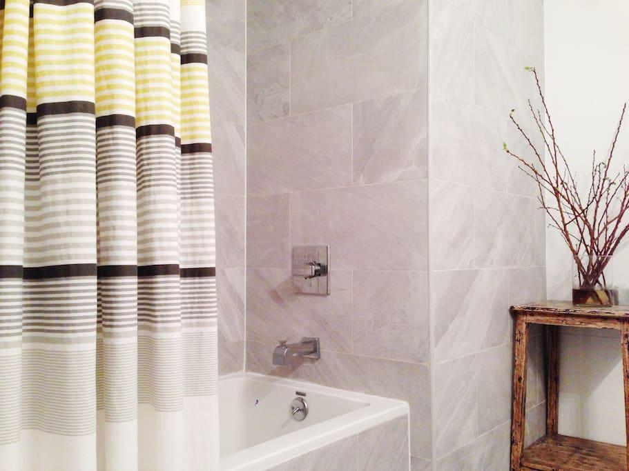 Deep soaking tub and all tile bathroom.