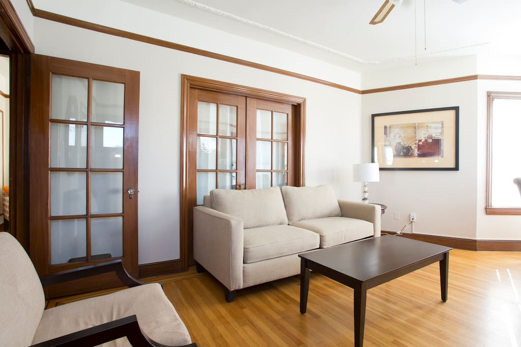 Comfortable living room and dining room, french doors to bedroom behind sofa