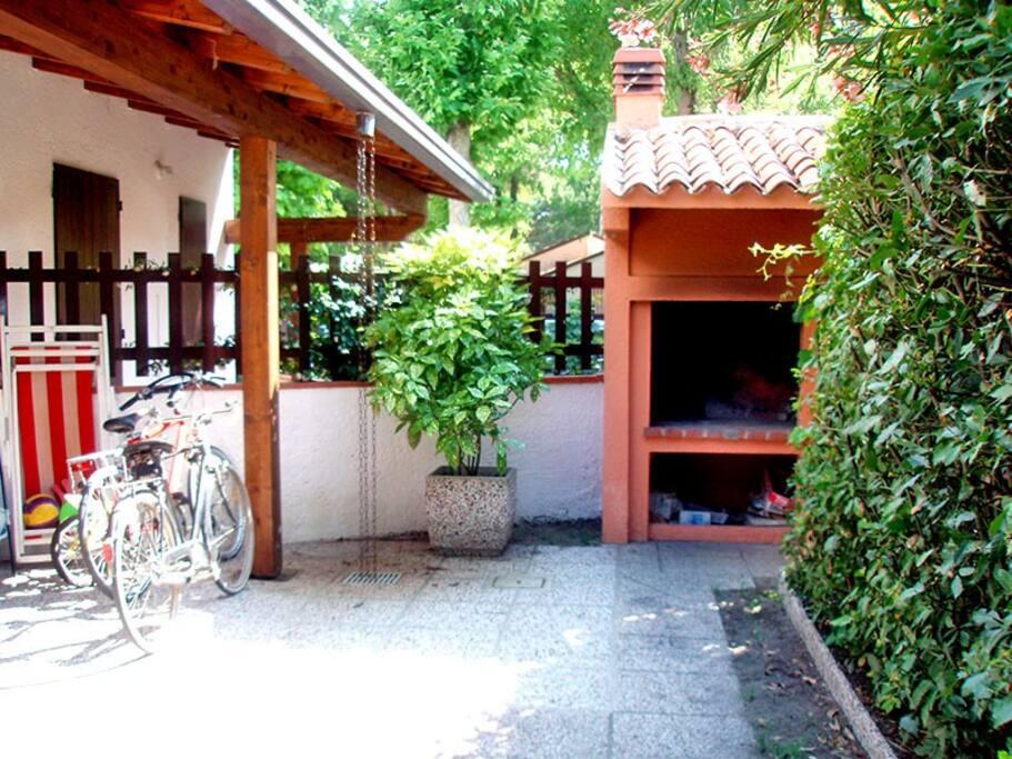 Giardino con patio arredato e barbecue