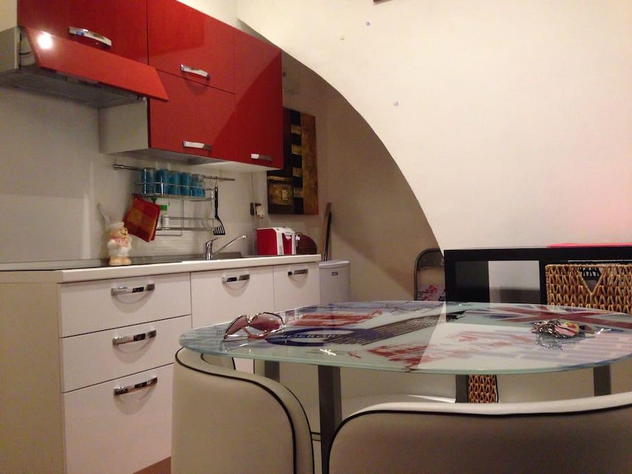 cucina composta da booster 4 fuochi, frigo, macchina per caffè a cialde, tavolino con poltroncine, ecc.