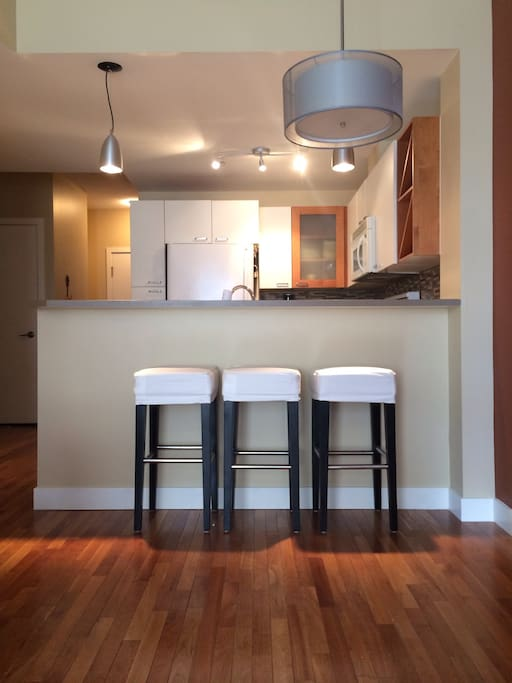 The open kitchen with 3 barstool and check out the fantastic hardwood!