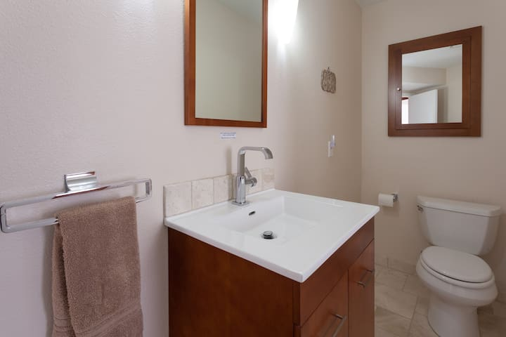 Private bathroom, with imported Turkish travertine tile, and contemporary vanities. Soft plush towels and bathing items provided for your use.