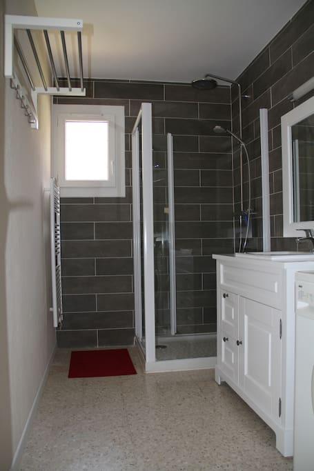 salle de bains avec une grande douche, lavabo et lave linge.