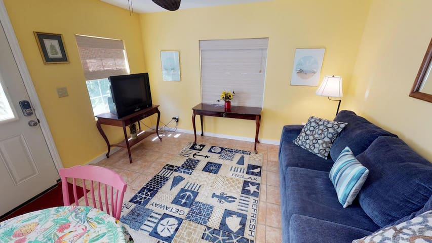 Living area with dining table, queen sleeper sofa, and TV