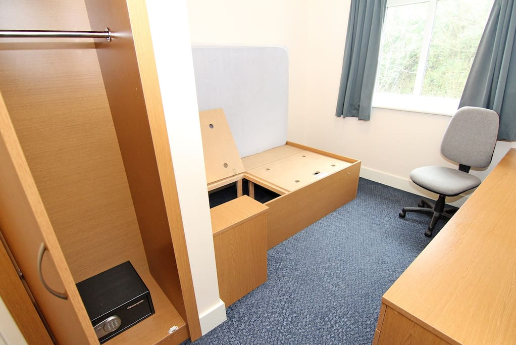 Standard 'Undressed' room with safe and storage. TV in communal living/kitchen area